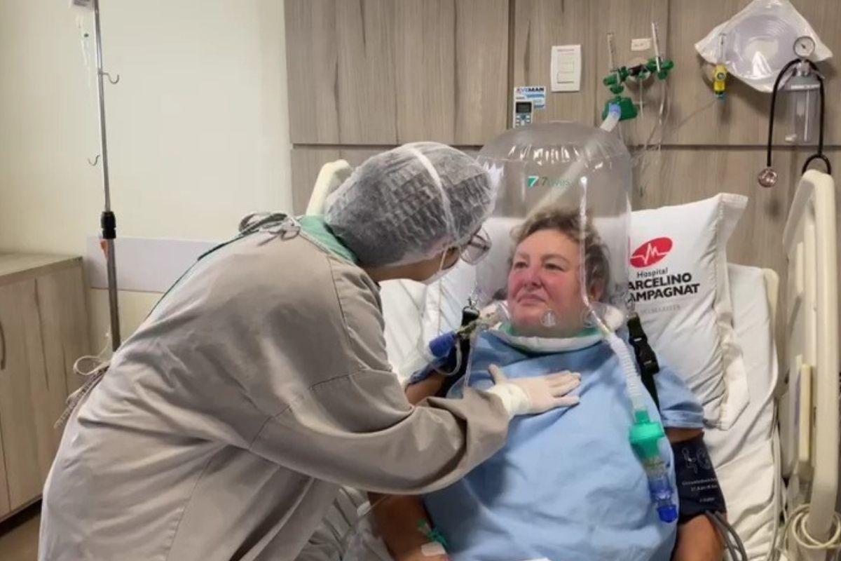 Elza Zawadzki utilizando o Helmet, cápsula respiratória que melhora a oxigenação dos pacientes
